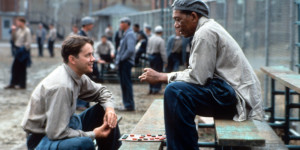 Tim Robbins and Morgan Freeman sitting outside on the benches playing checkers and talking in a scene from the film 'The Shawshank Redemption', 1994. (Photo by Castle Rock Entertainment/Getty Images)